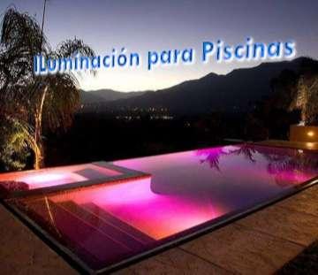 Piscina iluminada por la noche con focos led de color rosa con un fondo montañoso y palmera al fondo